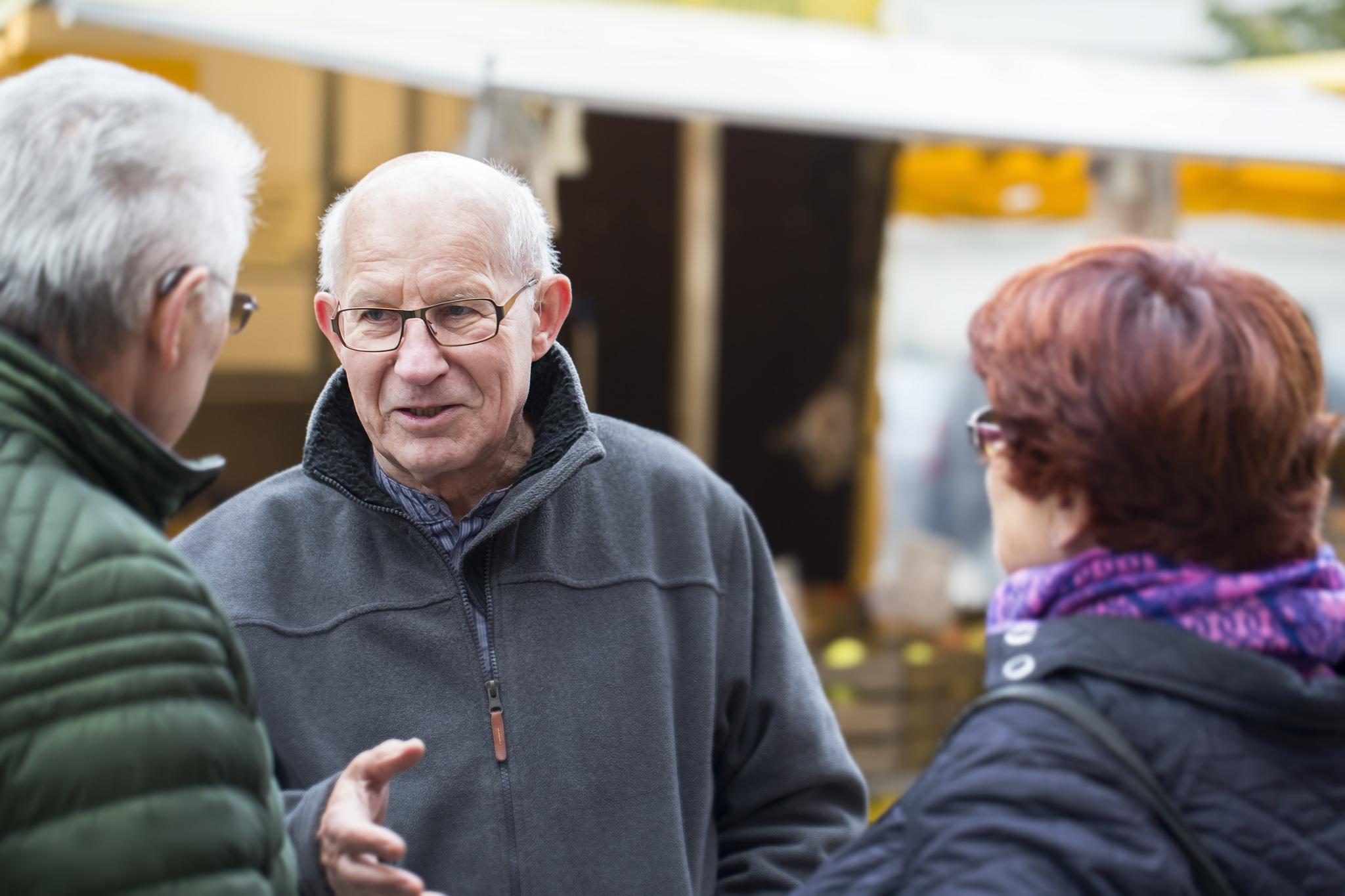 Drei Kunden mit kleinen Hörgeräten im Gespräch auf dem Markt in Hannover